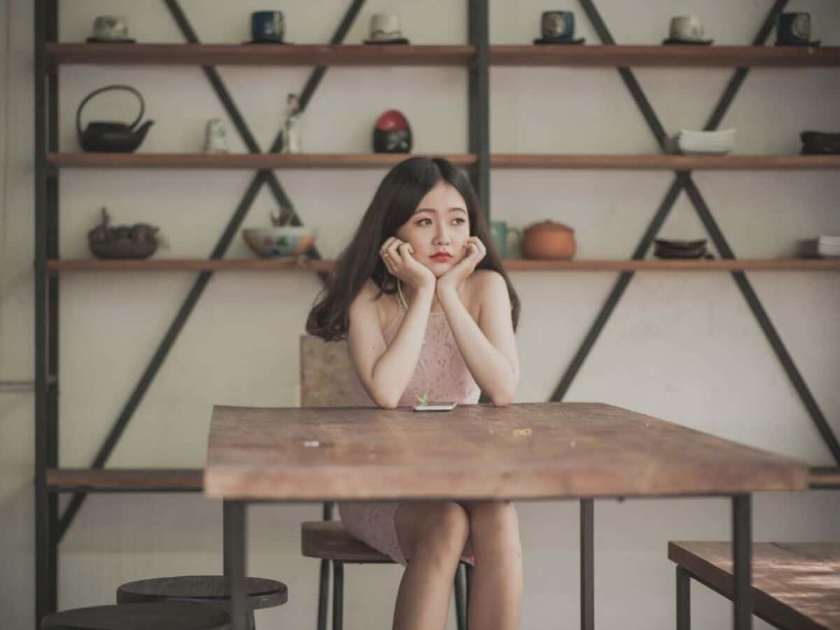 mlada zena sedi sama za stolom a hladi do neznama
